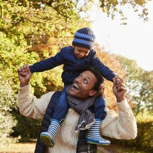Little boy sat on father's shoulders looking down and smiling at him, outside in a park