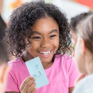 Girl smiling and holding up a card with a maths question on it. Symbolises maths interventions