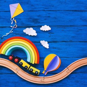 A colourful arty picture of a toy train with a rainbow and kites in the background