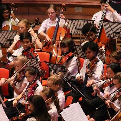 Services For Education concert taking place - children playing string instruments in an orchestra setting.