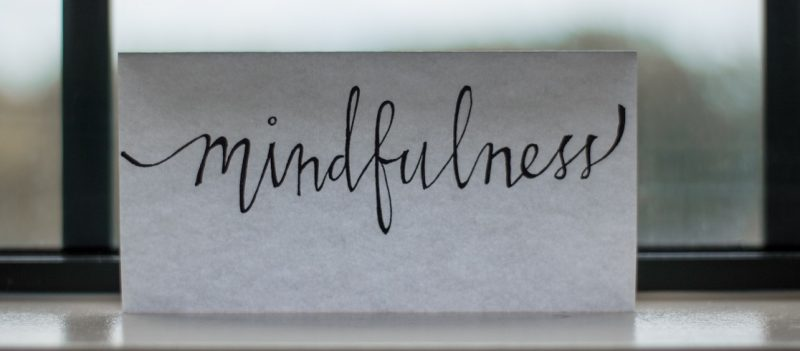 "An image of a piece of paper with the word ""mindfulness"" written on it."
