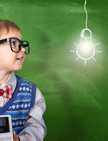 Little boy looking up at a painted image of a lightbulb on the wall, with a green background. Symbolising Services For Education school support