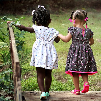 Two little girls walking away together as friends. Representing The Right to Feel Safe