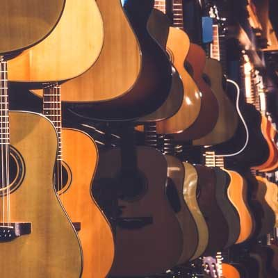 Guitars hanging up in a shop. School Bands/ Ensembles Support