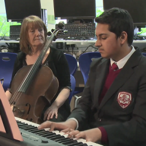 Boy playing piano with lady accompanying on cello. Symbolises Reel Music online music resources