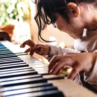 Little girl playing piano. Symbolising classroom Curriculum Primary Music Teacher