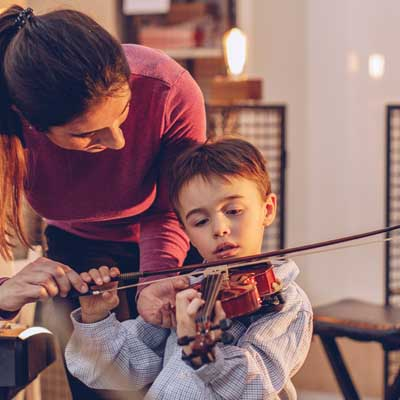 Little boy playing violin with teacher helping him. Representing WOW music weeks.