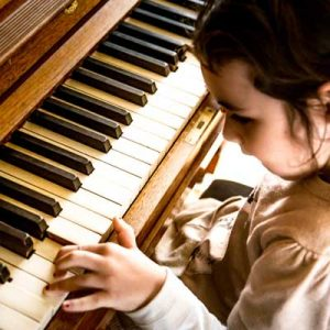 Little girl playing the piano. Symbolises Schools Instrumental/ Vocal Tuition