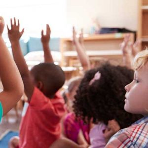 Kids all sat in a classroom with their hands up for the teacher. Representing EYFS Profile Standardisation and Moderation Training