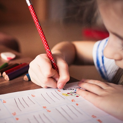 Little girl writing in an activity book. Representing Exploring the National Standard of Writing at Greater Depth within the Expected Standard (GDS) at End of KS2