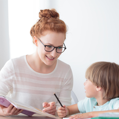 Woman teaching a little boy. Representing Phonics Screening Check – Administering the Check