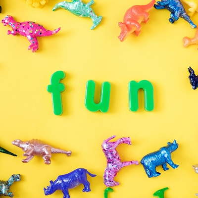 "Bright yellow background with green word ""fun"" and little colourful dinosaurs lying all around it. Representing Letters and Sounds in Nursery"