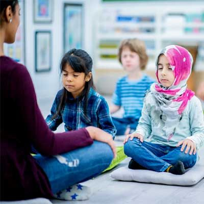 Picture of three pupils and a teacher sat cross legged with eyes closed in a classroom, meditating, represents an emotionally safe classroom