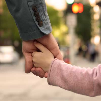 Little girl's hand holding an adult hand. Representing Attachment
