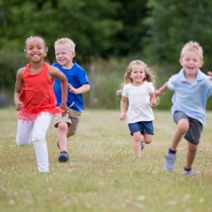 4 children running towards the camera looking happy. Representing surviving or thriving
