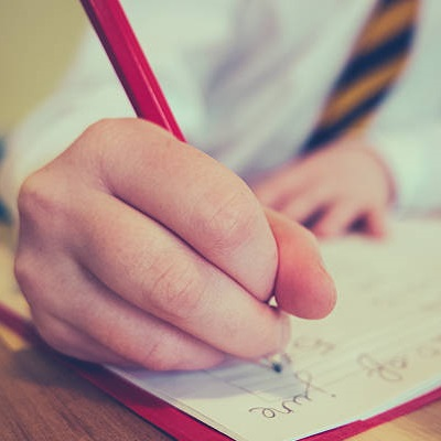 School girl writes in notebook. Representing Services For Education School Support peer moderation of english writing