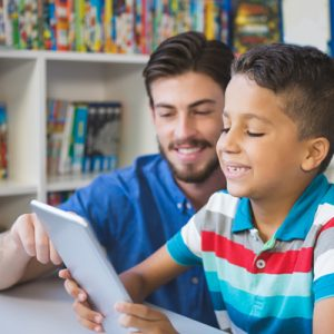 Little boy on an iPad with his teacher, both smiling. Representing Teaching Pupils With English as an Additional Language (EAL)
