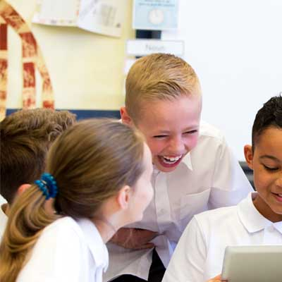 Image of some children reading from a computer and laughing with each other. Symbolises a year 2 classroom