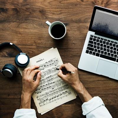 Music, earphones, laptop and coffee. Symbolising online music resources like Charanga.