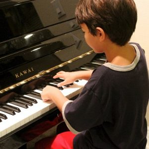 Picture of 2 children playing piano and another playing violin being taught by some teachers. Symbolising Reel Music