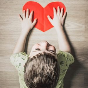 Artistic picture of a child lying forwards on the floor with a smile and holding down a red heart shaped piece of paper, symbolising british values