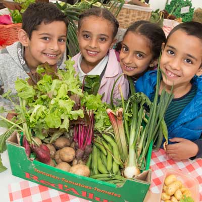 Children next to some lovely vegetables. Representing Health For Life Programme