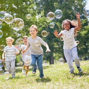 Group of friends with toothy smiles on their faces enjoying warm sunny day while participating in soap bubbles show, symbolises EYFS Profile Standardisation