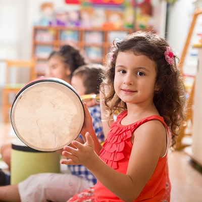 Little girl playing a drum looking at the camera