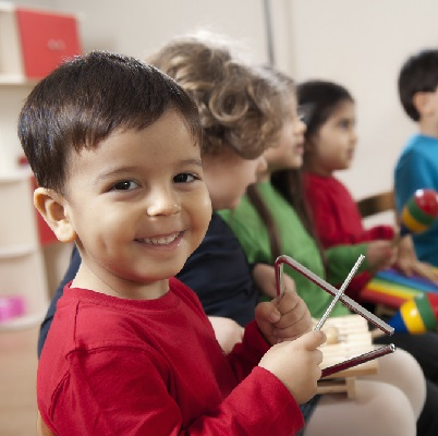 Little boy smiling at the camera and playing the triangle. Representing Soundtots