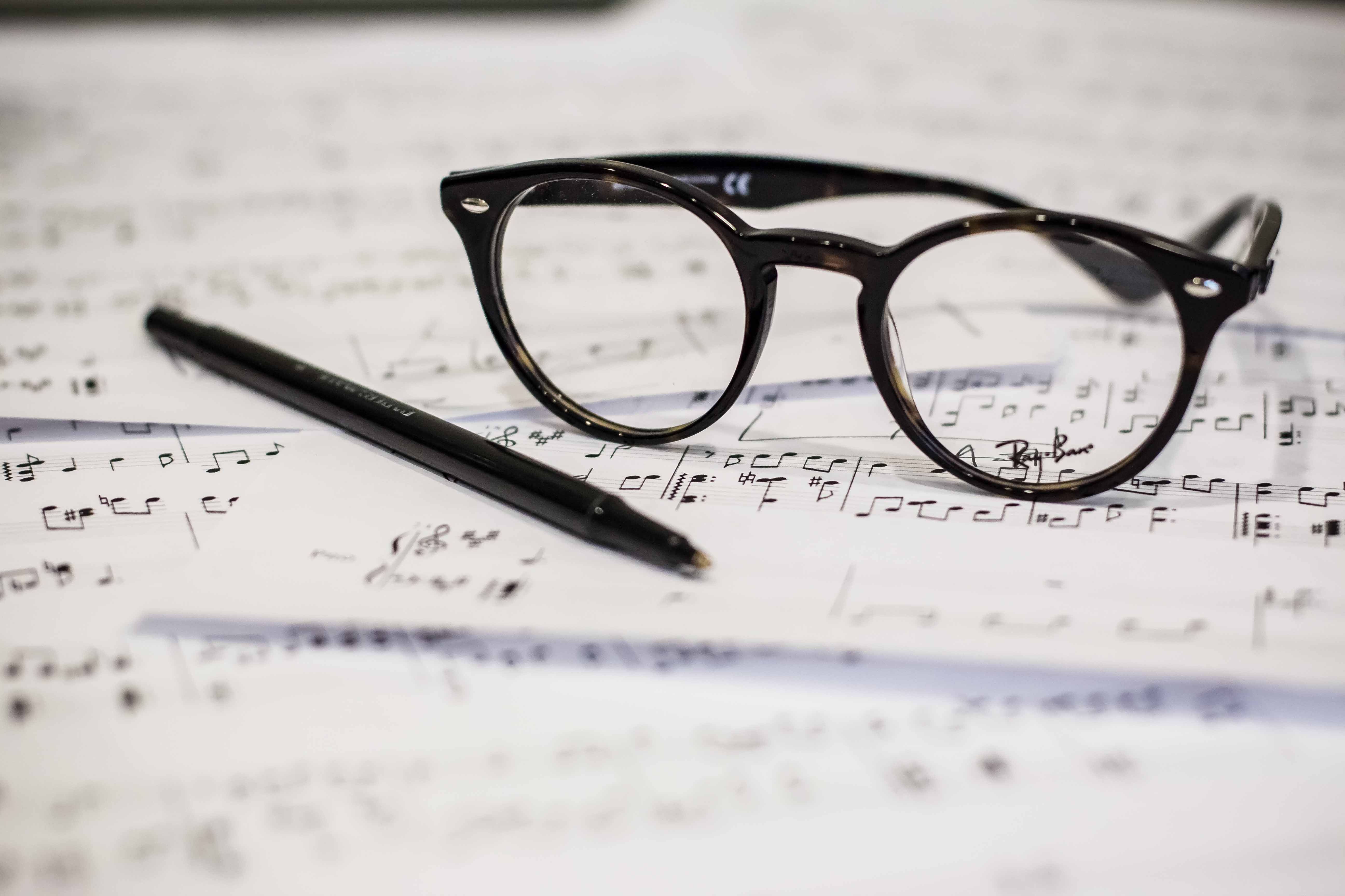 Glasses, pen and music sheets, ready for a music exam.
