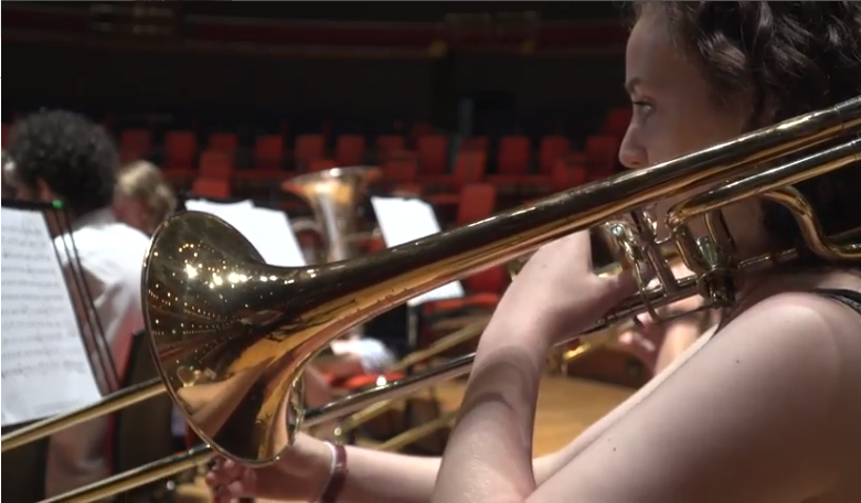 Image of a girl playing a trumpet at a music service concert