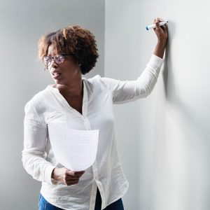 Picture of a woman writing on a white board wall, symbolising sta approved moderators - services for education