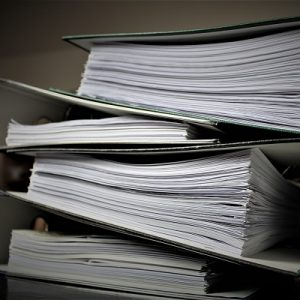 Picture of some folders, filled with files piled up. Symbolises statutory assessment and reporting.