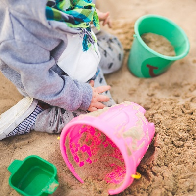 Child playing in a sandpit. Representing Developing the Outdoor Environment