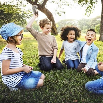 Children smiling, sat on the grass.