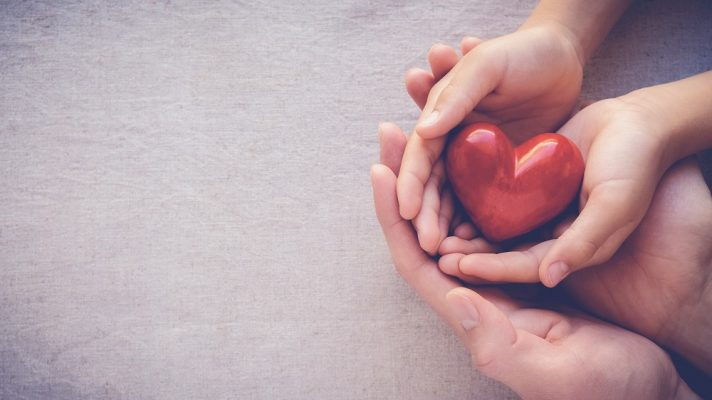 A picture of a child holding a heart and someone holding their hands