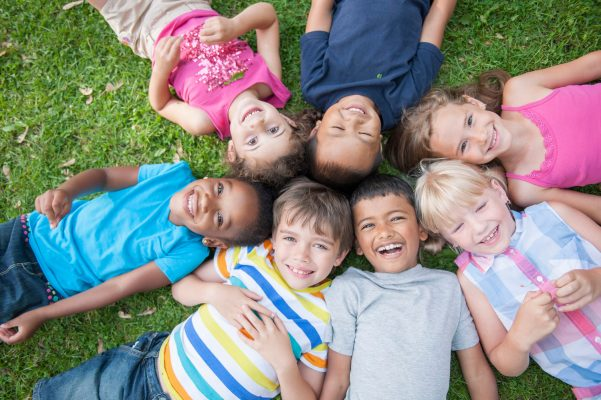 kids lying around in a circle looking happy - services for education