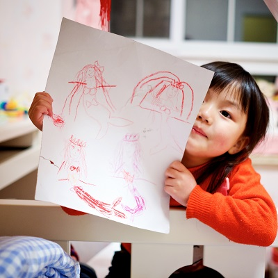 Picture of a little girl proudly showing her picture, Symbolising Continuous Provision: Maximising Children's Learning
