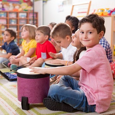 Children in a classroom playing drums, sat on the floor. Child smiling into camera. Symbolises Inspiring Sounds
