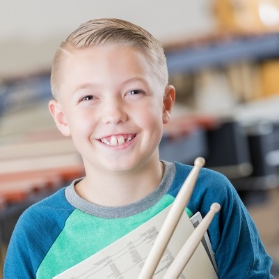 Picture of a boy smiling holding some drumsticks, symbolising The Music Cares Project