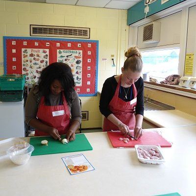 Picture of two health for life delegates cutting up food for a Health For Life practical