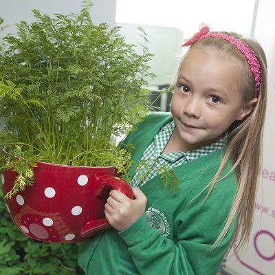 Little girl holding up a large teapot with plants growing in it.