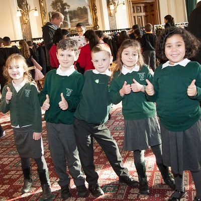 Picture of some children smiling with their thumbs up at a health for life event