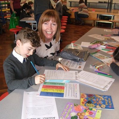 Picture of a mum and child filling out Health For Life booklets.