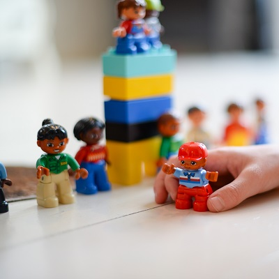 Child's hand playing with some lego bricks and people, symbolising pshe inset training