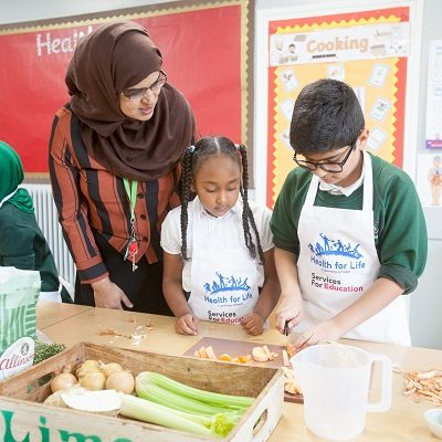Two children and a teacher taking part in a Health For Life practical, chopping up food