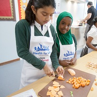 Two children chopping up sweet potatoes as part of a Health For Life practical
