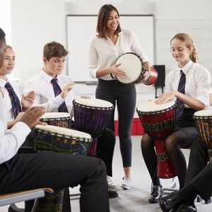 Group of kids taking part in a drum workshop in school.