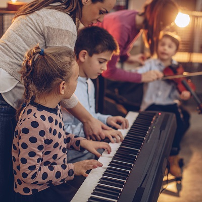 Children learning to play piano and violin in school