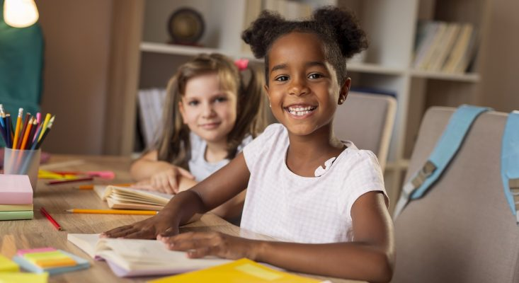 Two little girls smiling at the camera as they write in workbooks. Making Learning Stick - Curriculum 2019
